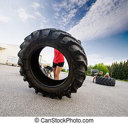 Athlete Flipping Large Tire - Female athlete flipping large...