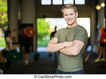Smiling Male Athlete Standing At Gym - Portrait of smiling...