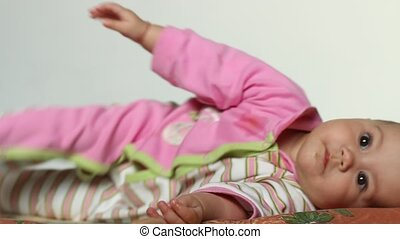 Cheerful Baby Twisting - Happy baby girl is twisting and...