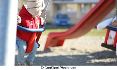 Children Park Swing Time - Little baby with hat on swings in...