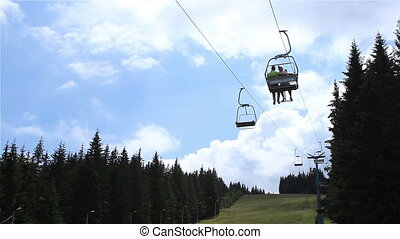 Chairlift over Fir Forest - Chairlift with tourists cross...