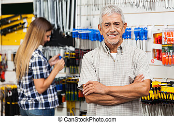 Confident Senior Man With Arms Crossed In Hardware Shop -...