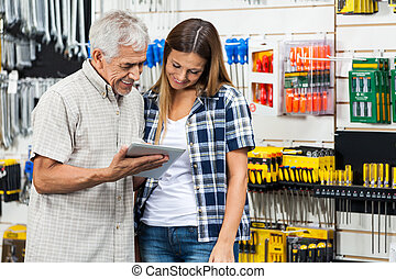 Family Using Digital Tablet In Hardware Shop - Father and...