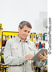 Man Using Tablet Computer In Hardware Store - Mature man...