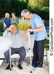 Male And Female Caretakers Helping Senior People - Male and...