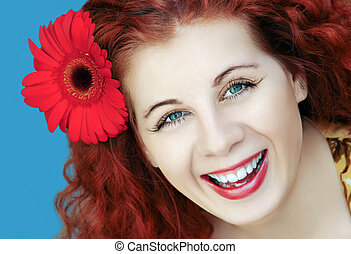 Portrait of red-haired woman with a flower