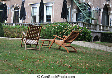 Wooden deckchairs - Two wooden deckchairs on the grass in...
