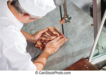 Butcher Cutting Fresh Meat With Bandsaw - High angle view of...