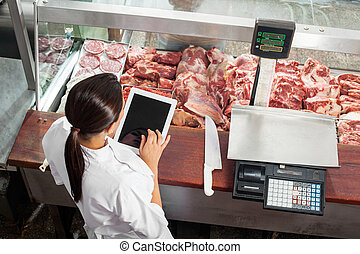 Butcher Using Digital Tablet In Butchery - High angle rear...
