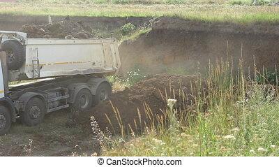Dump Truck Unloads - A dump truck unloads dirt for a...