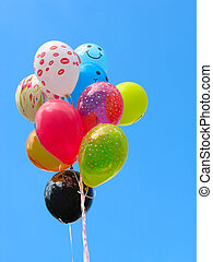 Bunch of colored party balloons against blue sky background