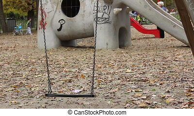 Empty Swing at Playgound - A fresh swing left swaying in the...