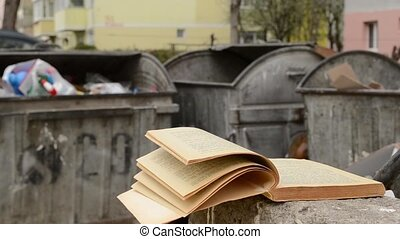 Yellowed Book and Dumpster - A yellowed book left near the...