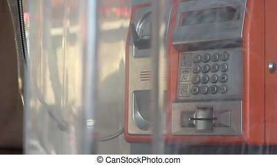 End Call Close Up - In a phone booth a person hangs up call...
