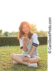young teen woman sitting on grass field with smart phone in...