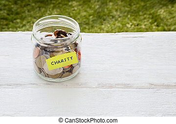 Charity money distribution - World coins in money glass jar...