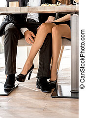Legs of a couple sitting at the restaurant - Young couple...