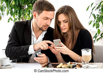 Young couple paying for ther order at the restaurant - Young...
