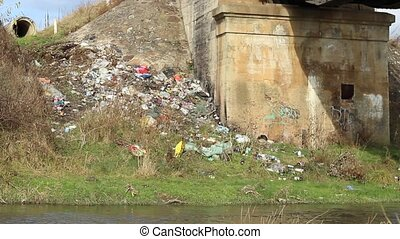 Garbage Along River - On a river banks, near a bridge an a...