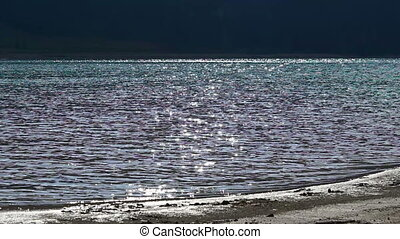 Flashes on Lake Shore - Sun shines and reflects onto the...