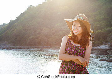 portrait of beautiful young woman wearing wide straw hat...