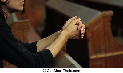 Girl Praying in Church - Girl dressed in black shirt...