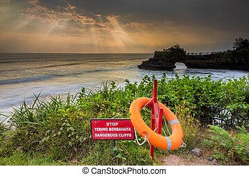 Warning Sign at a cliff and ray of lights at pura batu...