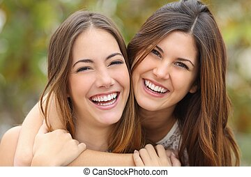 Two women friends laughing with a perfect white teeth with a...