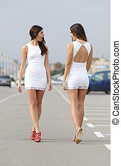 Two women with the same dress looking each other with hate -...
