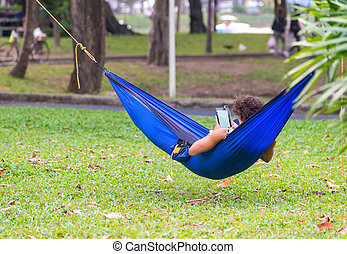 man lying on hammock in garden with tablet computer