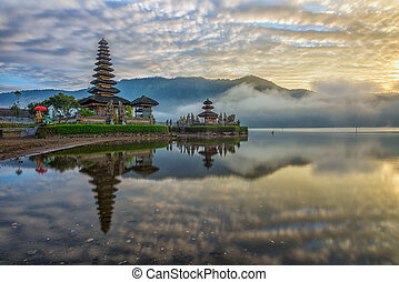 A reflection of a pura temple at sunrise - Pura Ulun Danu...