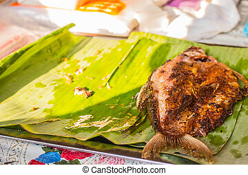 Pickled fish in banana leaves on the table