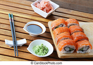 sushi with salmon and avocado on wooden background