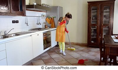 Young woman cleaning the kitchen fl - A young housewife is...