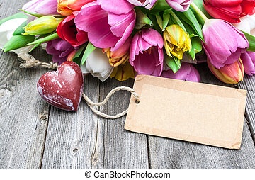 Bouquet of tulips with an empty tag and red heart on wooden...