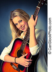 Portrait of young blonde guitar player woman - studio...