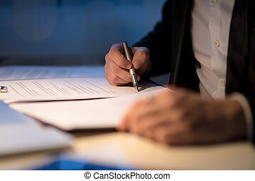 Businessman working late signing a document or contract in a...