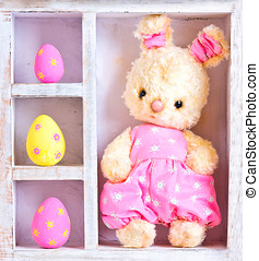 Rabbit bunny toy and easter eggs on the case - Rabbit bunny...