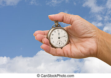 Time Management - A pocket watch in hand on a sky...