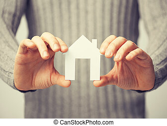 man holding paper house - bright picture of man holding...