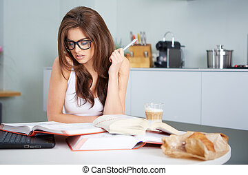 Happy young woman studying in kitchen - a happy young woman...