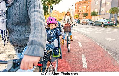 Lttle girl with helmet on head sitting in bike seat