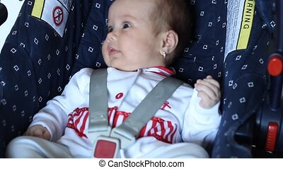 Little Baby on Car Seat - Little baby girls is seating on a...