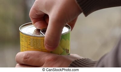 Man Opens Canned Food - Person opens a can of food. <br...