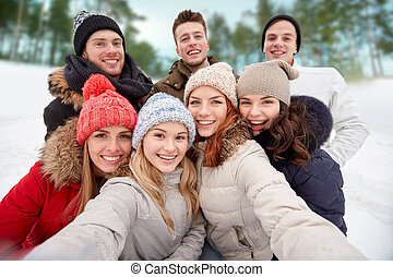 group of smiling friends taking selfie outdoors - winter,...
