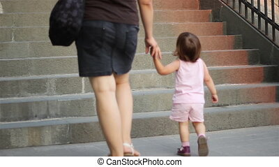 Little Girl Climbing Stairs - A little girl with her mother...