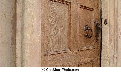 Man Uses Door Knocker - Man uses the wrought iron door...