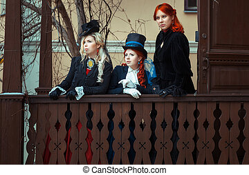 Girls in retro outfits - Three girls standing on his...