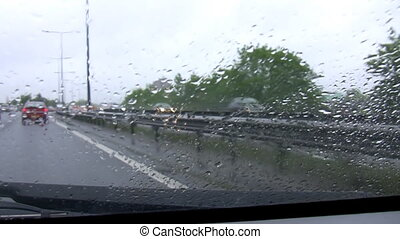 Busy motorway on a rainy day - Car front window view of...
