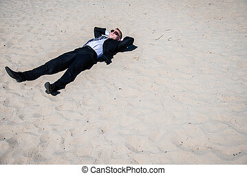 business - A man in a business suit sunning on the beach